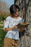 Beautiful young woman reading a book outside Stock Image