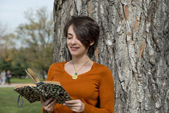 Beautiful young woman reading a book outside Stock Photo