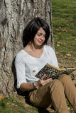 Beautiful young woman reading a book outside Royalty Free Stock Images