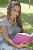 Beautiful young woman reading book in park Royalty Free Stock Image