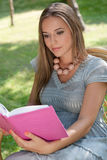 Beautiful young woman reading book in park Stock Image