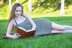 Beautiful young woman reading book at park. Young woman reading book at park Stock Photography