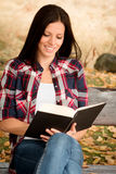 Beautiful young woman reading a book in park at fall. Beautiful young woman reading a book sitting on a bench in park at fall Royalty Free Stock Photos