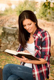 Beautiful young woman reading a book in park at fall. Beautiful young woman reading a book sitting on a bench in park at fall Stock Image