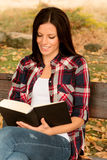 Beautiful young woman reading a book in park at fall. Beautiful young woman reading a book sitting on a bench in park at fall Royalty Free Stock Image