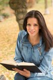 Beautiful young woman reading a book in park at fall. Beautiful young woman reading a book sitting on a bench in park at fall Stock Photos