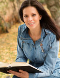Beautiful young woman reading a book in park at fall. Beautiful young woman reading a book sitting on a bench in park at fall Royalty Free Stock Images
