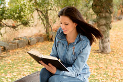 Beautiful young woman reading a book in park at fall. Beautiful young woman reading a book sitting on a bench in park at fall Royalty Free Stock Photo