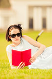 Beautiful young woman reading book in the park Stock Photos
