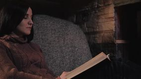 Beautiful Young Woman Reading Book Sitting By Fireplace In a Country House. Close Up Shot, Holiday And Lifestyle Concept stock video footage