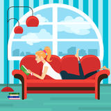 Beautiful young woman reading book on sofa Royalty Free Stock Photography