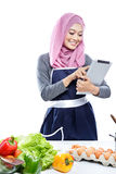 Beautiful young  woman reading cooking recipe on tablet while ma Royalty Free Stock Photos