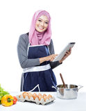 Beautiful young  woman reading cooking recipe on tablet while ma Royalty Free Stock Photography