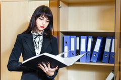 Beautiful young woman reading documents in office. Royalty Free Stock Photo
