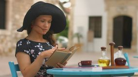 Beautiful young woman reading interesting book, marking favorite places with pen. Stock footage stock video