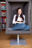 Beautiful young woman reading in library Royalty Free Stock Image