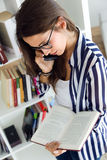 Beautiful young woman reading in the library. Royalty Free Stock Images