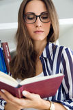 Beautiful young woman reading in the library. Portrait of beautiful young woman reading in the library Stock Image