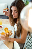 Beautiful young woman reading the news and enjoying breakfast. Stock Image