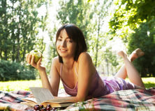 Beautiful young woman reading outdoor Stock Photography