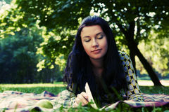 Beautiful young woman reading outdoor Royalty Free Stock Image