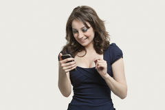 Beautiful young woman reading text message on cell phone over gray background Royalty Free Stock Images