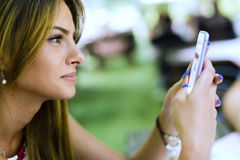 Beautiful young woman reading text messages and smiling Stock Photography