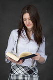 Beautiful young woman reads big book on black Stock Images