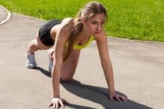 Beautiful young woman ready to run. Beautiful young woman getting ready to run from lying pose stock images