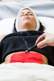 Beautiful young woman receiving alternative therapy in spa. Royalty Free Stock Image
