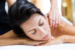Beautiful young woman receiving a back massage in a spa. Stock Image