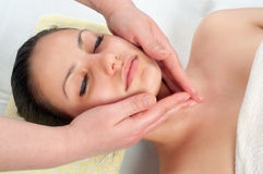Beautiful young woman receiving a face massage Royalty Free Stock Images
