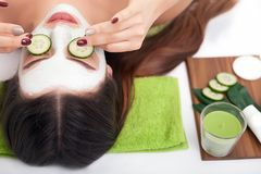 Beautiful young woman receiving facial mask of cucumber. Beautiful young woman receiving facial mask of cucumber royalty free stock photography