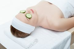 Beautiful young woman receiving facial mask of. Cucumber in beauty salon, closeup isolated on white Stock Photos