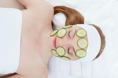 Beautiful young woman receiving facial mask of Stock Photo