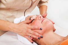Beautiful young woman receiving facial massage Stock Images