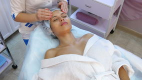 Beautiful young woman receiving facial massage with closed eyes in a spa salon.
