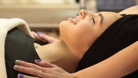 Beautiful young woman receiving facial massage with closed eyes in a spa salon. Hd stock video footage