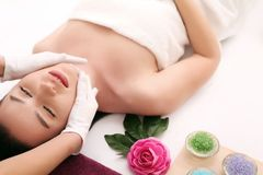 Beautiful young woman receiving facial massage in spa salon.  stock photos