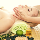 Beautiful young woman receiving facial massage at a spa salon. A beautiful young woman receiving facial massage at a spa salon. Perfect Skin. Skincare. Young royalty free stock photos