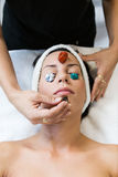 Beautiful young woman receiving gemstone therapy in spa. Stock Photos