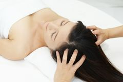 Woman in spa salon receives head massage Royalty Free Stock Photo