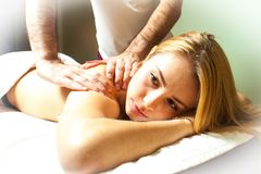Beautiful young woman receiving massage in spa stock photography