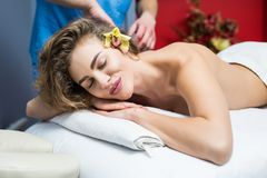 Beautiful young woman receiving a relaxing back massage at spa. royalty free stock image