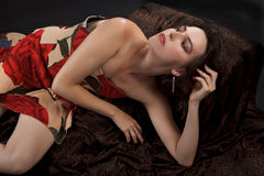 Beautiful young woman reclines in strapless dress. Beautiful young dark haired woman in sexy strapless long dress, printed with big red roses, and red satin high Royalty Free Stock Photos