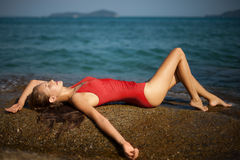 Beautiful woman in red bikini lying and sunbathing Royalty Free Stock Images