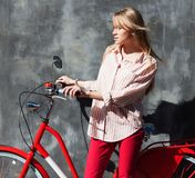 Beautiful young woman in red chino holding hands on her red vintage bicycle, standing against gray wall. Outdoors Stock Photos