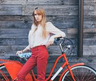 Beautiful young woman in red chino holding hands on her vintage bicycle and looking at camera with smile while standing against ol. D wood planks. Outdoors Stock Photos