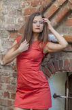 Beautiful young woman in a red cocktail dress short walk from the old house Stock Photo