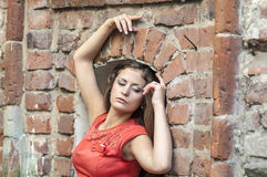 Beautiful young woman in a red cocktail dress short walk from the old house Royalty Free Stock Photos